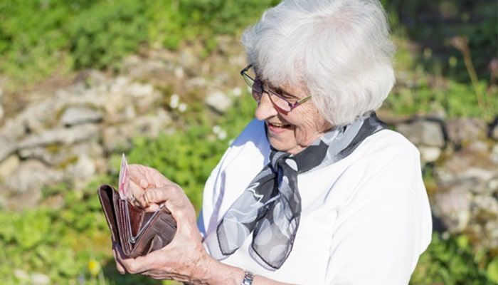 Mujer anciana mirando su cartera