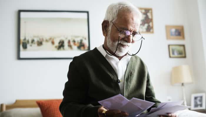 Pensionista mirando fotos de sus hijos