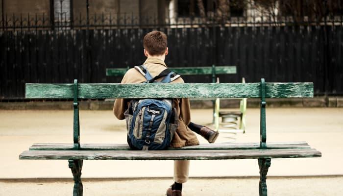 joven sentado en un banco de la calle