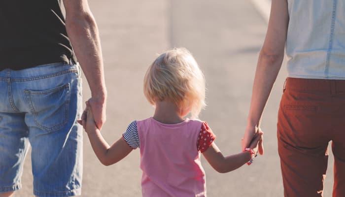 Padres con su hija de la mano