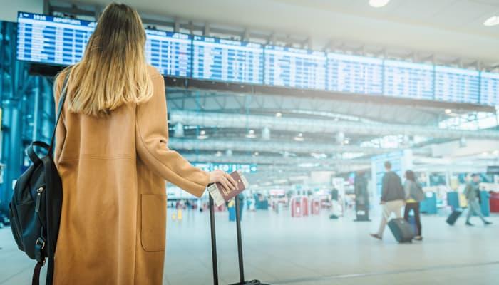 Mujer esperando con sus maletas para viajar