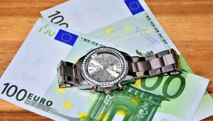 billetes de 100 euros y reloj de tiempo