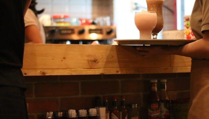 Camarera sirviendo bebidas en la bandeja