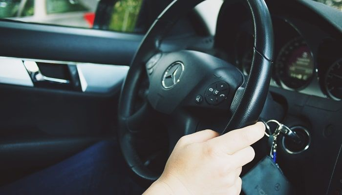 Manos al volante de un conductor en un coche Mercedes