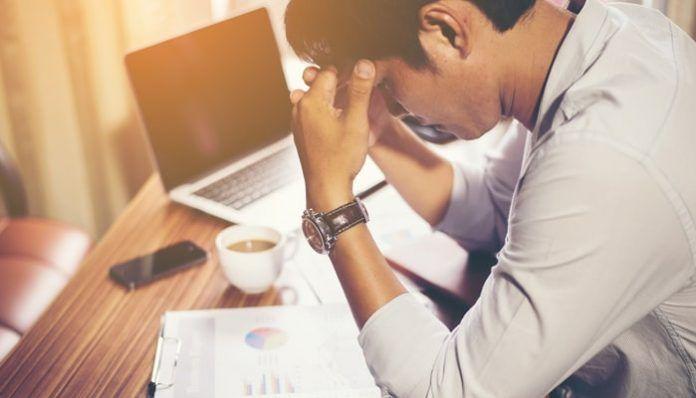 Hombre mirando documentos junto al ordenador