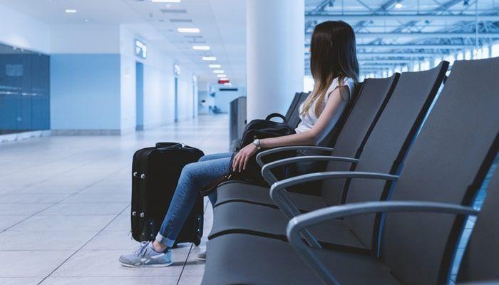 Mujer con maleta esperando en el aeropuerto
